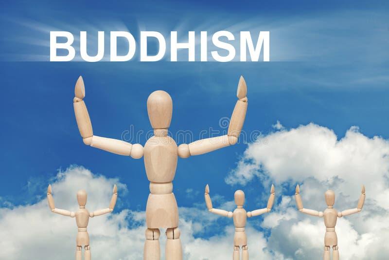 Träfalsk docka på himmelbakgrund med text BUDDISM arkivfoto