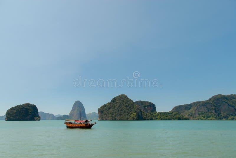 Träfartyg nära kalkstenöar i havet i Thailand royaltyfri fotografi