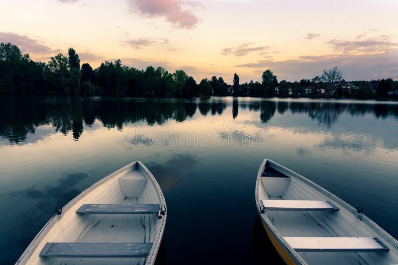 Träfartyg på en lugna sjö kallade Csonakazo sjön i den Szombathely Ungern på skymning efter solnedgång fotografering för bildbyråer