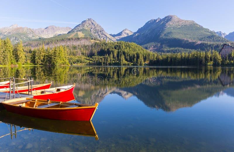träfartyg på pir i en bergsjö fotografering för bildbyråer