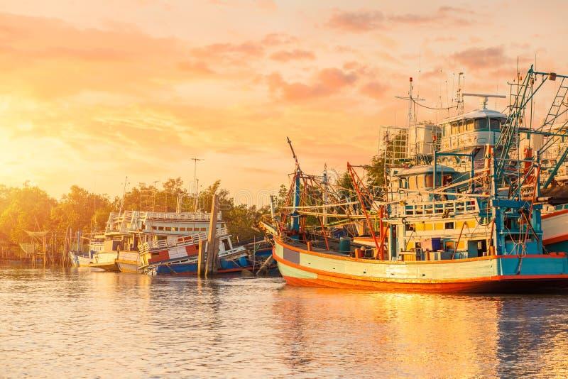 Träfiskebåt i floden och solnedgång, soluppgång med det härliga molnet arkivfoto