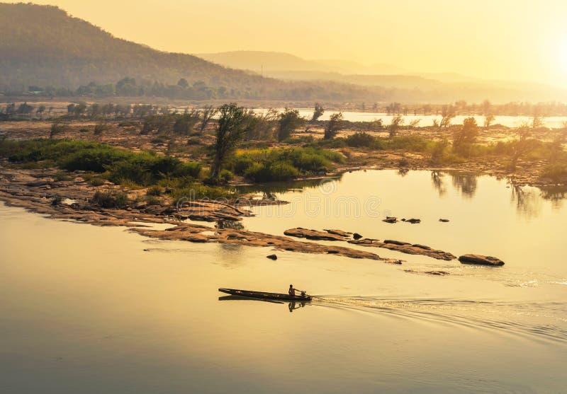 Träfiskebåtsegling i Mekong River på soluppgång på gränsen av Thailand och Laos royaltyfri fotografi