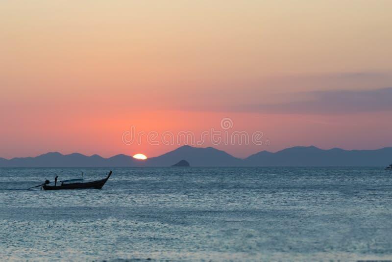 Träfiskebåtsegling på havet, mot bakgrunden av solnedgången och bergen arkivbilder