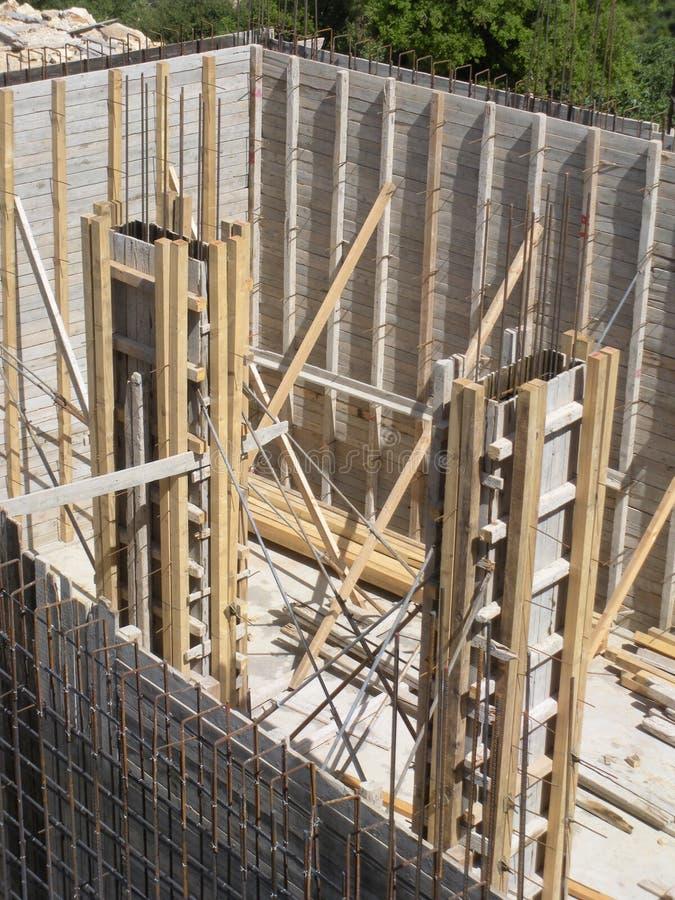 Träformer inneslutar kolonner för förstärkt betong på en konstruktionsplats royaltyfria bilder