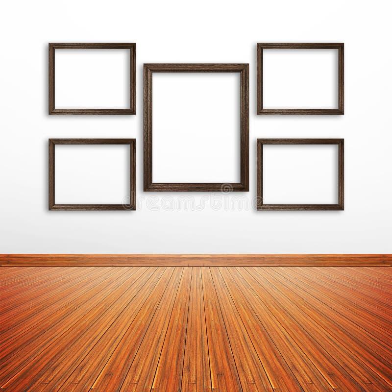 Träfotoramar på den vita väggen inom rummet royaltyfri fotografi