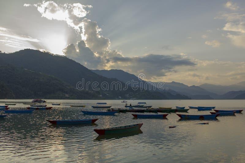 Trägamla tomma blåa fartyg på Phewa sjön på bakgrunden av en bergdal i dimman royaltyfri foto