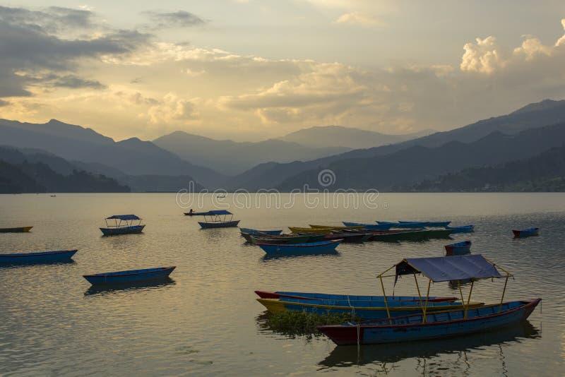 Trägamla tomma blåa fartyg på sjön Phewa på bakgrunden av en bergdal i dimman och aftonhimlen royaltyfria foton