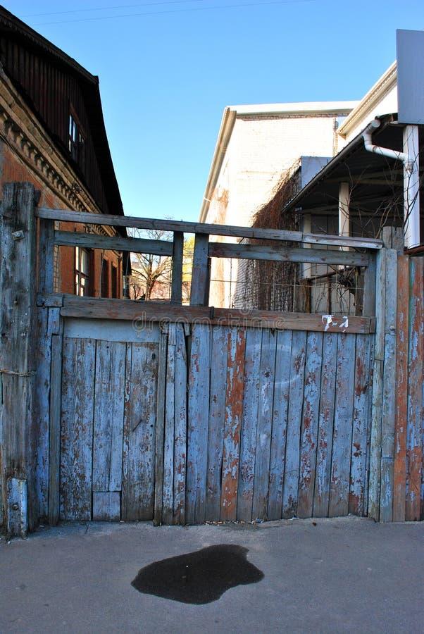 Trägammal port till gården som målas med blå sjaskig målarfärg, en pöl av svart målarfärg på ingången arkivfoto