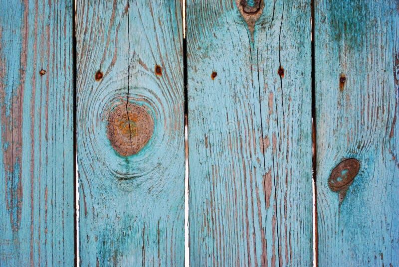 Trägammal rostig staketyttersida som målas med sjaskig målarfärg för turkos och, spikar royaltyfri foto
