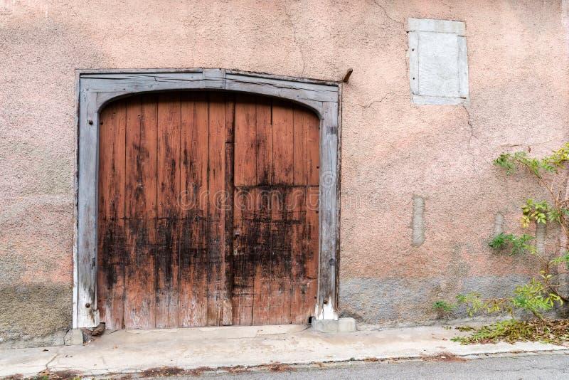 Trägaragedörr eller port för stor tappning i en historisk rosa husfasad med en grön vinrankaväxt på sidan fotografering för bildbyråer