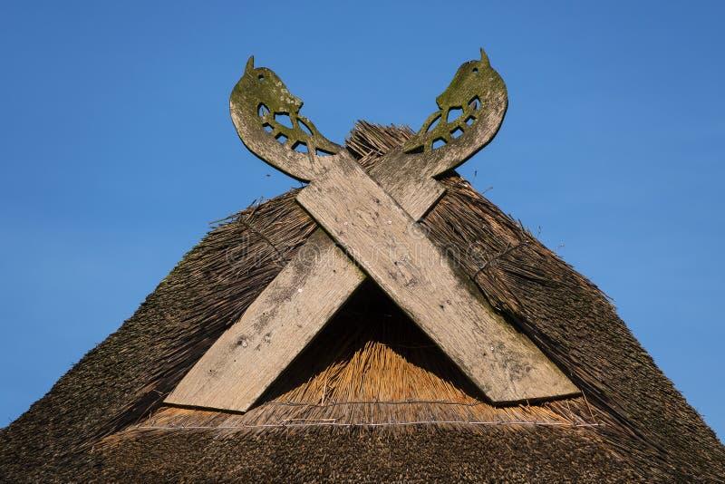 Trägavelförsedda bräden i form av hästhuvud på en halmtäckt ro royaltyfri fotografi