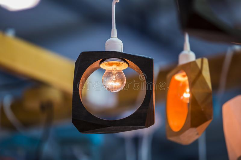 Trägeometrisk formljuskrona med en edison lampa Svart och gul märkes- ljuskrona royaltyfri foto