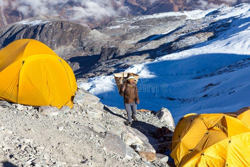 Träger Nepalesen Sherpa, der Weidenkorb im Gebirgsexpeditions-Lager trägt lizenzfreies stockbild
