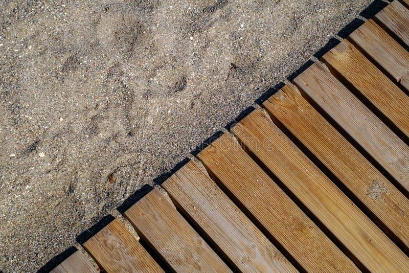 Trägolv på den sandiga stranden royaltyfri foto