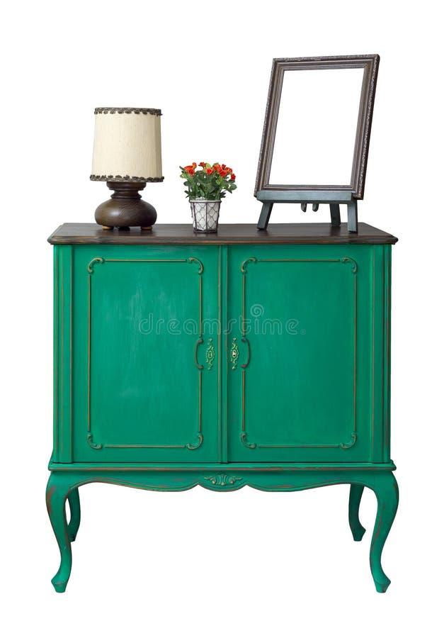 Trägrön tappningserveringsbord med den tomma skrivbords- fotoramen, blommaplanteren och den isolerade tabelllampan på vit med den royaltyfria foton