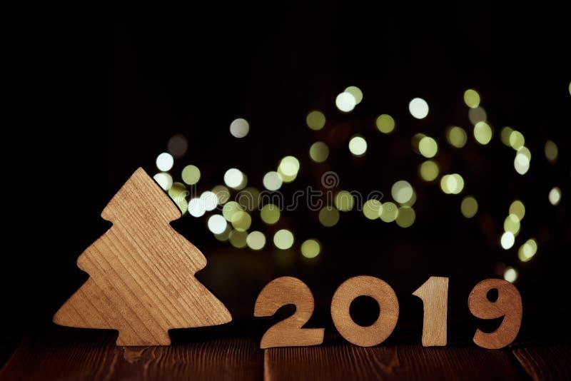 Trägranträd och text 2019 från trädiagram på mörk träbakgrund med den LEDDE ljusa girlanden den konstnärliga detaljerade eiffel r arkivbild