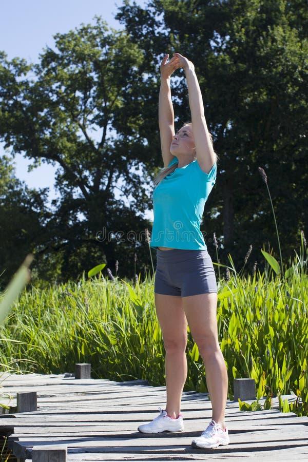 Trägt das blonde Mädchen zur Schau, das ihre Arme für Körperenergie, draußen ausdehnt stockfoto