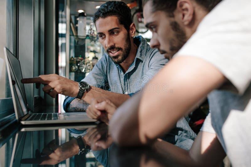 Trägt den Ladenbesitzer zur Schau, der Ideen mit dem Kollegen bespricht, der Computer verwendet lizenzfreie stockbilder
