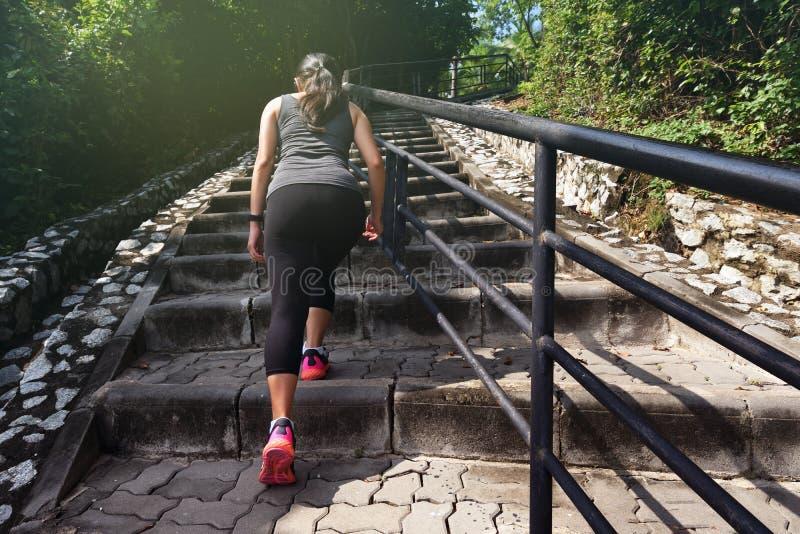 Trägt die Frau zur Schau, die auf Steintreppe steigt stockbild