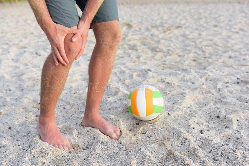 Trägt Knieverletzung auf dem Mann zur Schau, der Strandvolleyball spielt stockfoto
