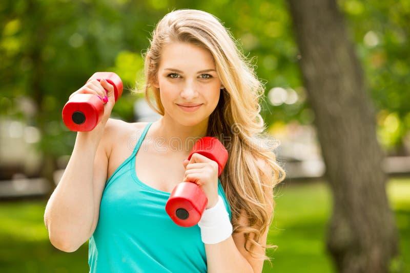 Trägt Mädchenübung mit Dummköpfen im Park zur Schau stockfoto