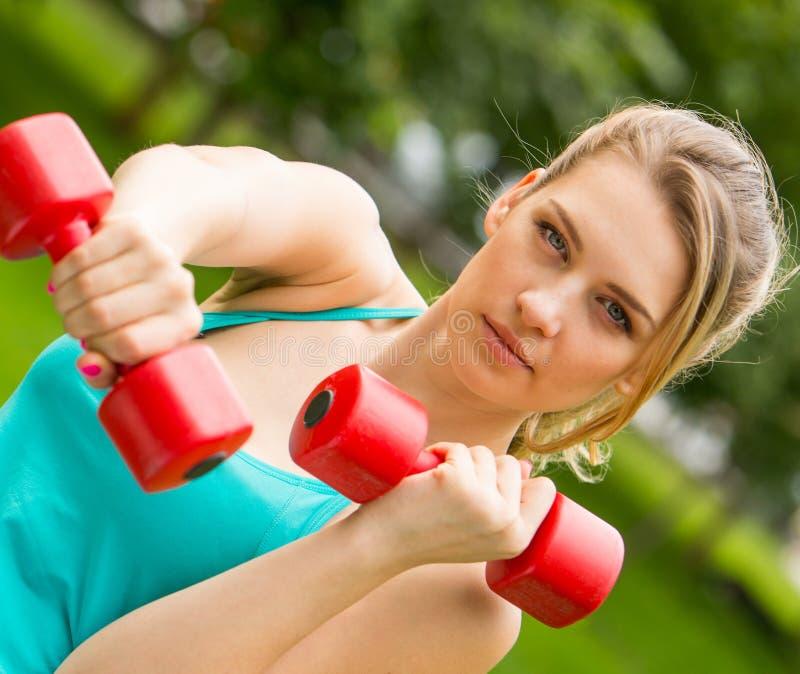 Trägt Mädchenübung mit Dummköpfen im Park zur Schau lizenzfreie stockbilder