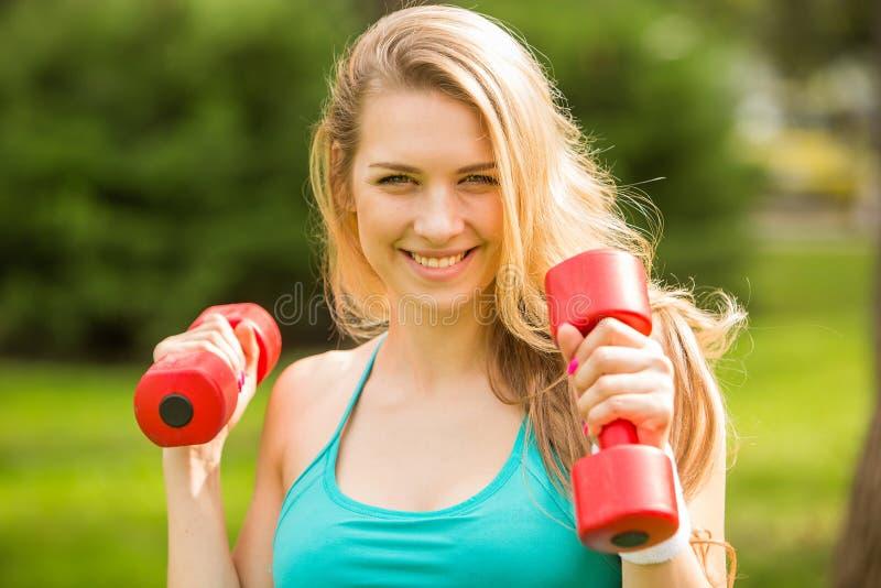 Trägt Mädchenübung mit Dummköpfen im Park zur Schau lizenzfreie stockfotos