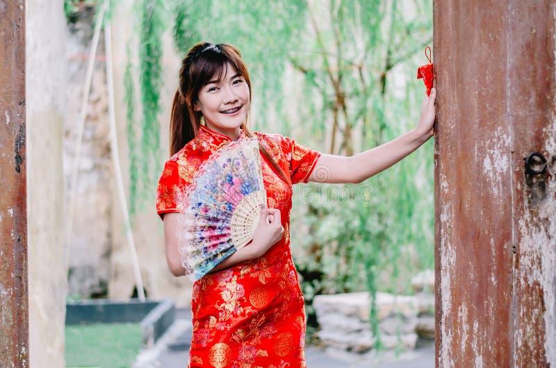 Trägt schönes Lächeln der jungen Frau des Porträts cheongsam tiefrotes Kleid, das einen Fan hält, der Kamera schaut Festlichkeite stockfotos
