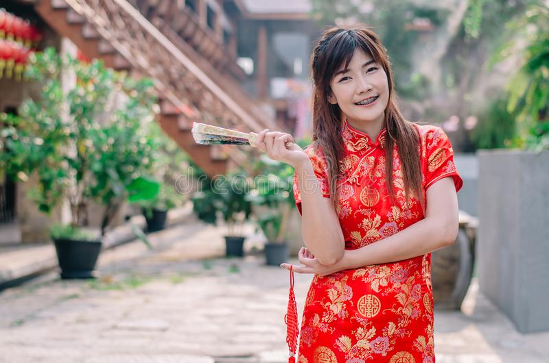 Trägt schönes Lächeln der jungen Frau des Porträts cheongsam tiefrotes Kleid, das einen Fan hält, der Kamera schaut Festlichkeite stockfoto
