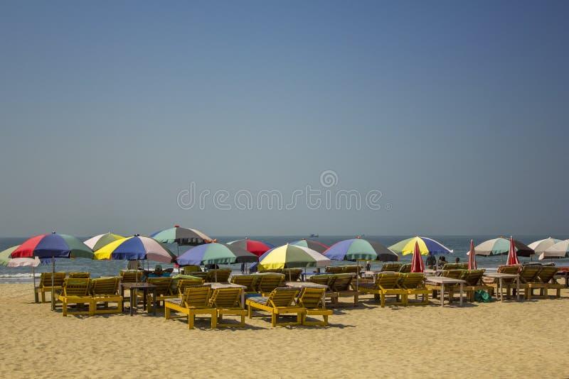 Trägula stranddagdrivare under ljusa mång--färgade solparaplyer på sanden mot havet under en klar blå himmel royaltyfria bilder
