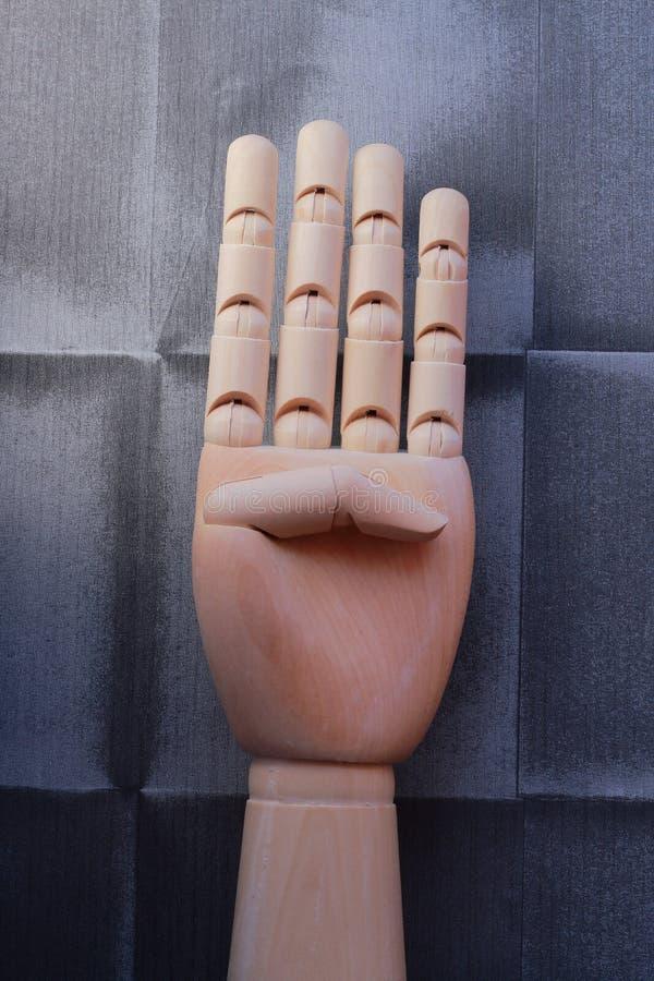 Trähand med fyra lyftta fingrar royaltyfria foton