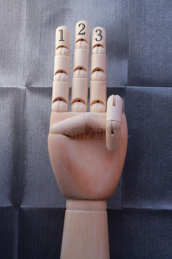 Trähand med tre fingrar som lyfts och numreras med nummer en, två och tre arkivfoto