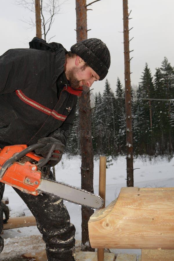 Trähem- byggnad, journal för chainsawbladklipp av trä arkivbilder