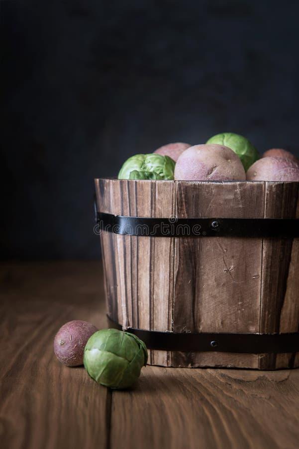 Trähink med små rå kålar och potatisar arkivfoto