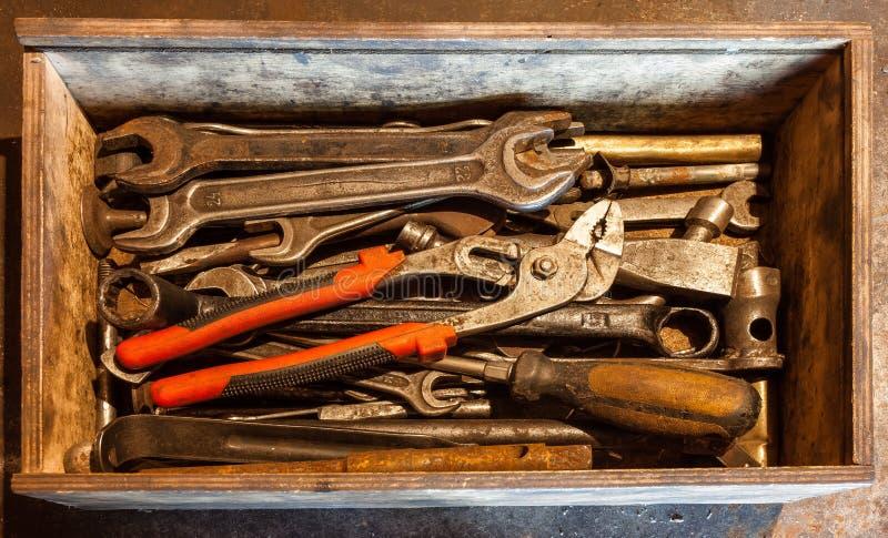 Trähjälpmedelasken av handhjälpmedel med gamla och smutsiga rostiga skiftnycklar, cirkelskruvnycklar, plattång, skruvmejslar, stä arkivfoton
