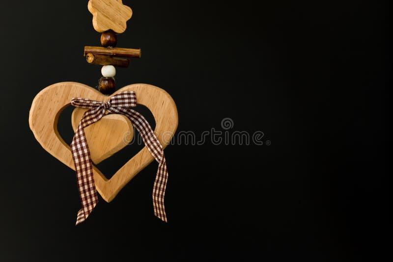 Trähjärta på ett rep med träbollar, en pilbåge i mitt, s arkivbilder