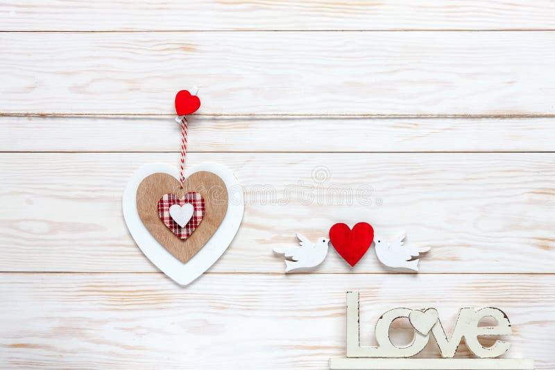 Trähjärta på rep, bokstäver förälskelse och statyetter av duvor med hjärtor Begrepp för valentin dag, bröllop, koppling och royaltyfri fotografi
