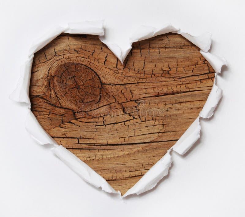 Trähjärta. Rivit sönder pappers- hål i hjärta Shape med gammalt trä royaltyfri fotografi