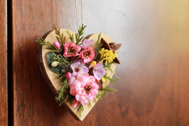 Trähjärta smyckade med konstgjorda färgrika blommor som hänger på den hemliga dörren royaltyfri foto