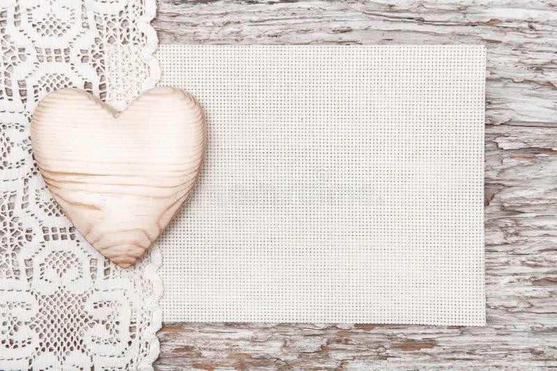 Trähjärta, spets- torkduk och kanfas på gammalt trä royaltyfri bild