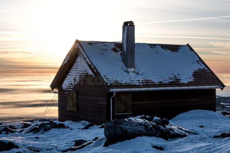 Trähus överst av berget Hisnande solnedgång som förbluffar himmel, moln royaltyfri foto