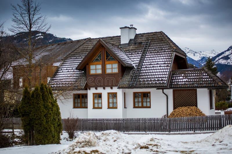 Trähus i österrikiska fjällängar på den snöig dagen royaltyfri bild