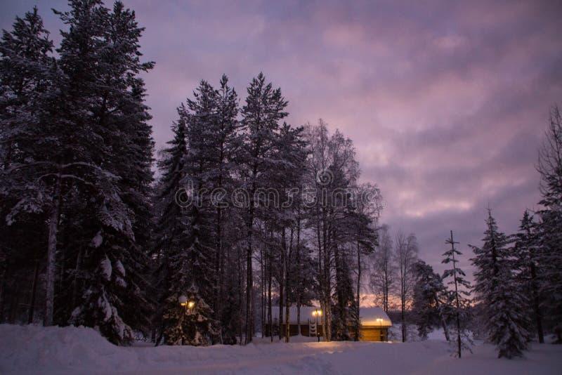 Trähus i aftonen i vinter royaltyfria foton