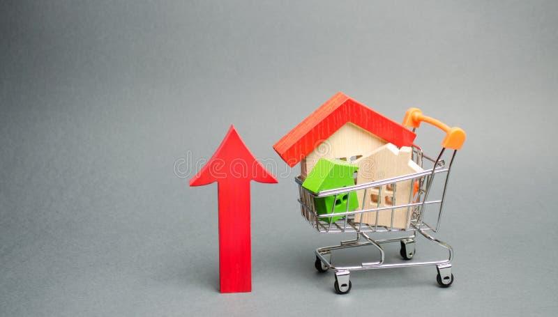 Trähus i en shoppa vagn och en röd pil upp Begreppet av att ?ka kostnaden av hus H?g beg?ran f?r fastighet _ royaltyfri foto
