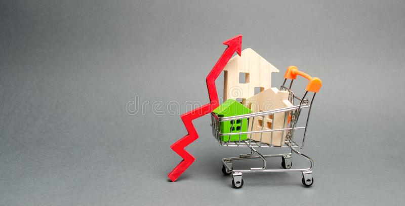 Trähus i en shoppa vagn och en röd pil upp Begreppet av att ?ka kostnaden av hus H?g beg?ran f?r fastighet _ royaltyfria foton