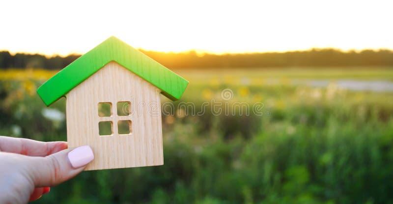 Trähus i händerna i solnedgångbakgrunden verkligt begreppsgods Eco v?nskapsmatchhem Symbol av lyckligt familjeliv arkivfoton
