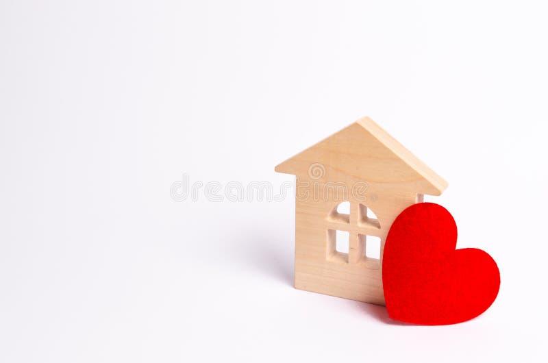 Trähus med en röd hjärta på en vit bakgrund Förälskelserede, förälskelseförhållanden Köpa ett hus med en ung familj royaltyfri fotografi