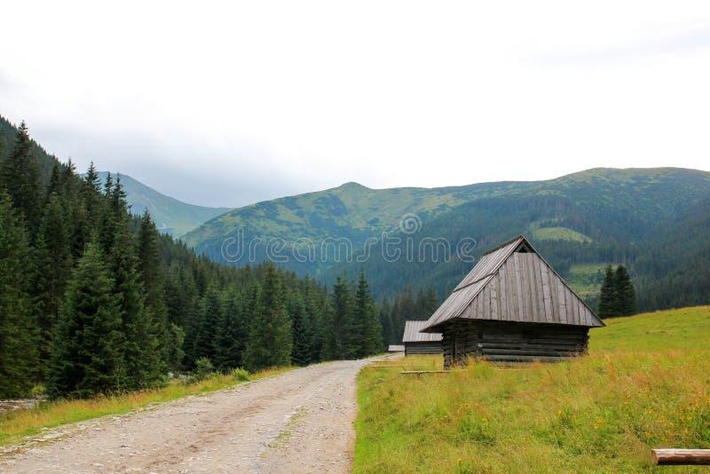 Trähus nära vägen bland bergen arkivbild