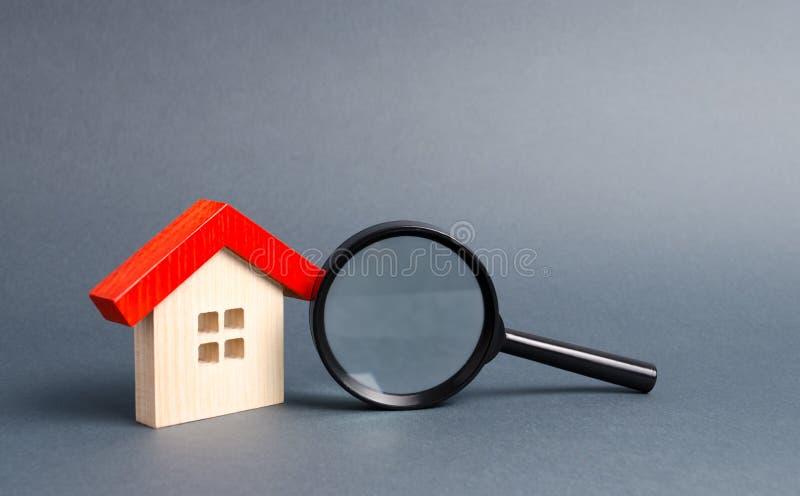 Trähus och förstoringsglas på en grå bakgrund K?pa och s?lja fastigheten, byggnadsnybyggen, kontor och hem arkivfoton