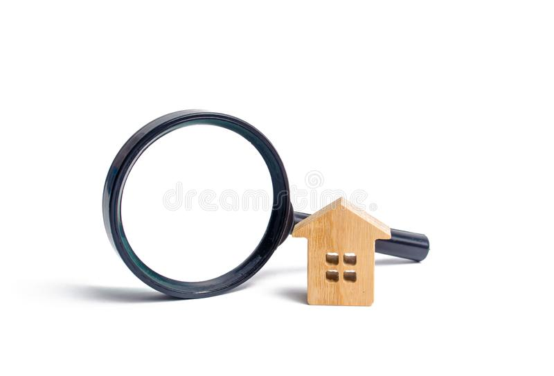 Trähus och förstoringsglas på en vit bakgrund Köpa och sälja fastigheten, byggnadsnybyggen, kontor och hem royaltyfri fotografi